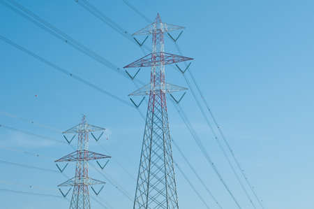 against the current: Pylons of steel that are used to carry electrical current silhouetted against the sky, italy