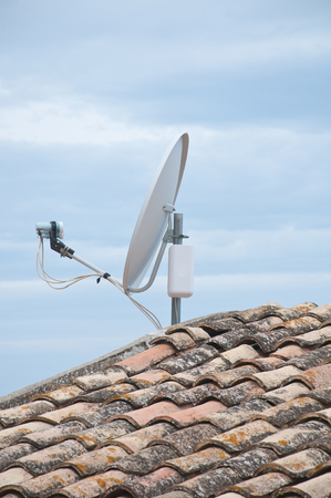 plant design: Roof of a house with tiles and satellite dish Stock Photo