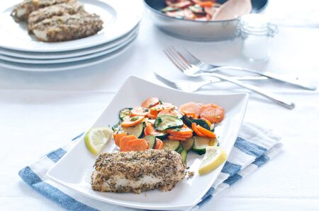 breading: cod with spicy breading served with carrots and zucchini