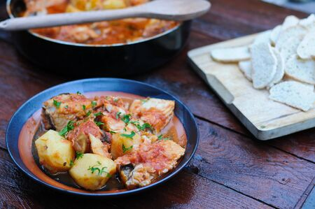 cod cooked in a pan with tomato, olives and potatoes,italy Stock Photo