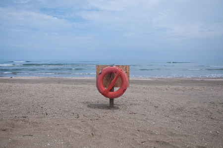 attached: red life buoy attached to a pole on the beach