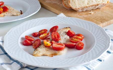 Sea bass fillet baked with cherry tomatoes,italy Stock Photo