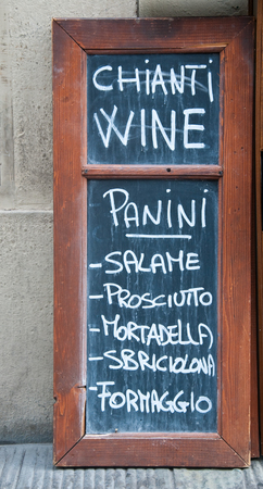 a sign indicating the sale of sandwiches, wine, ham, cheese, and mortadella in florence