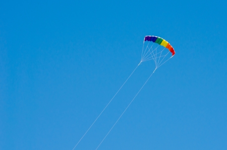 Colorful kite flying in a clear blue sky photo