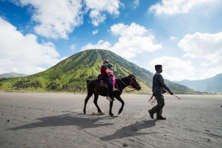 Oost-Java, Indonesië-05 mei: Toeristen rijden het paard op de berg Bromo, de actieve Bromo vulkaan is een van de meest bezochte toeristische attracties en een deel van de Tengger-massief op mei 05,2013 in Oost-Java, Indonesië.