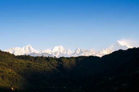 alpenglow: Mount Kanchenjunga range of the himalayas at first light of sunrise at Sikkim , India