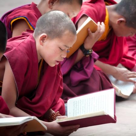 GANGTOK, SIKKIM, INDIA - AUG 19: An Unidentified Tibetan lama prays mantra at Ramtek Monastery on August 19, 2012 in Gungtok, Sikkim, India