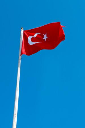 brandish: Waving flag of Turkey under sunny blue sky