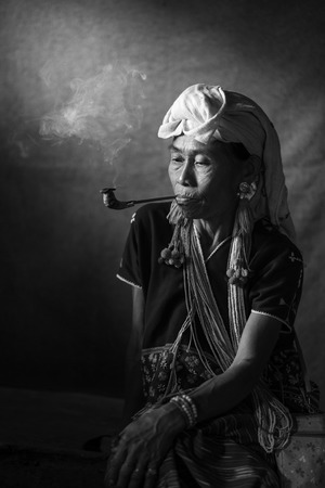CHIANG MAI, THAILAND - JUL 25 : Karen hill tribe is smoking tobacco pipe with traditional clothes and dramatic light on July 25, 2015 in Chiang Mai, Thailand.
