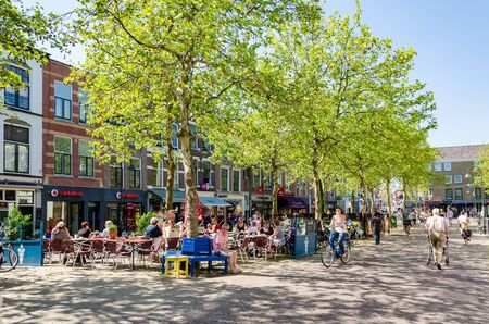 delft: DELFT,THE NETHERLANDS - APRIL 16: People in City of Delft on April 16, 2014 , the Netherlands. Delft is known for its historic town centre with canals and a popular touristic destination. Editorial