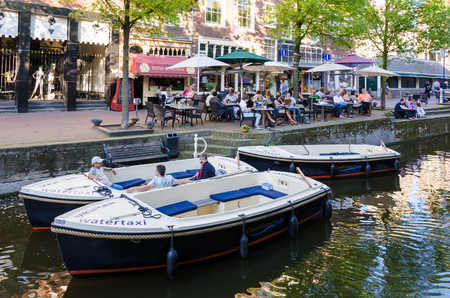 delft: DELFT,THE NETHERLANDS - APRIL 16: Tourists in City of Delft on April 16, 2014 , the Netherlands. Delft is known for its historic town centre with canals and a popular touristic destination.