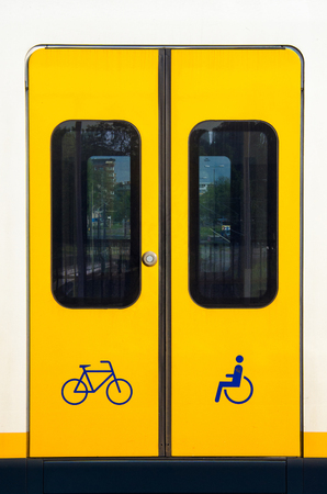 Detail of a yellow sliding door with bicycle and wheelchair symbol on a modern train.