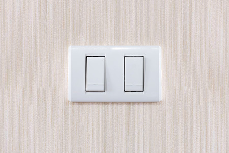 light switch: Modern light switch on a creamy wallpaper background Stock Photo