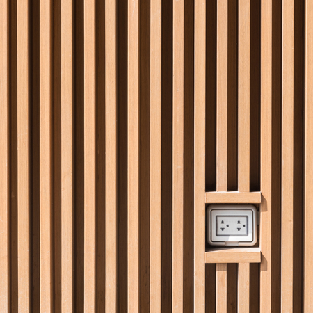 grounded plug: Plug socket on light brown wooden wall pattern at outdoor installation