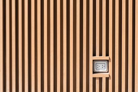 plug socket: Plug socket on light brown wooden wall pattern at outdoor installation