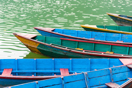 phewa: Colourful attraction Boats docked at the Phewa lake in Pokhara, Nepal. Selective focus at middle boat