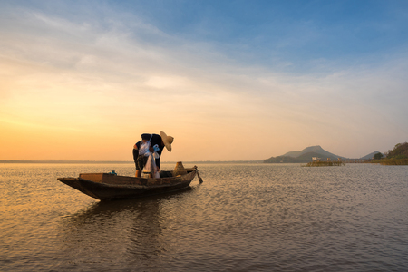 Asian fisherman on wooden boat preparing a net for catching freshwater fish in nature river in the early morning before sunrise Banque d'images