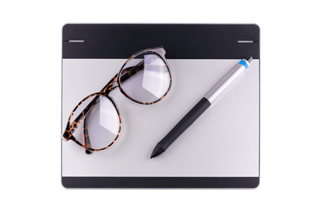 illustrators: Top view of graphic tablet with pen and retro glass isolated on white background. For illustrators, photographer and designers