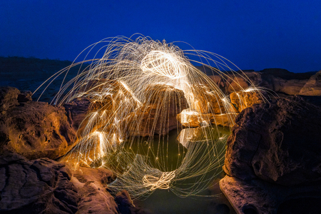 rock wool: Long exposure capture of Burning steel wool being spun before dusk on a grand canyon rock field of Thailand Stock Photo