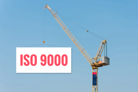 standard steel: Industrial Construction crane holding a billboard with ISO9000 text on blue sky background. Stock Photo