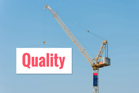 standard steel: Industrial Construction crane holding a billboard with Quality text on blue sky background.