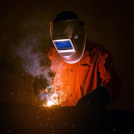 安全装置と防護マスク建設工場で鉄骨の溶接産業労働者。
