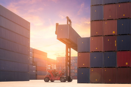 Forklift truck lifting cargo container in shipping yard or dock yard against sunrise sky with cargo container stack in background for transportation import,export and logistic industrial concept