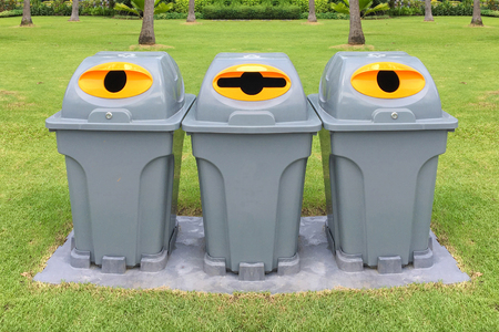 waste products: Three plastic recycle bins to separate different waste products in park Stock Photo