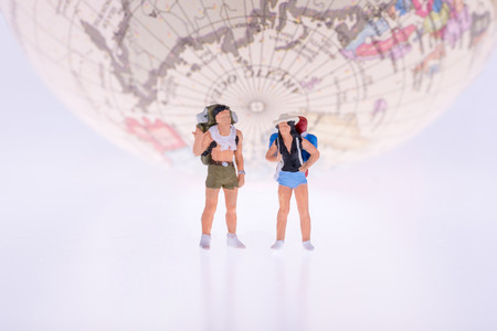 globetrotter: Close up of Miniature backpacker and tourist people with earth in background for travel concept Stock Photo
