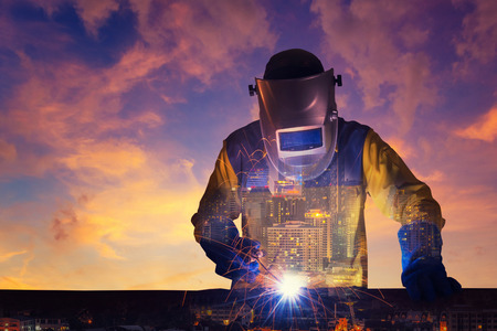 Double exposure of a downtown city and Industrial Worker welding steel structure with sunset sky in background for industrial and construction concept