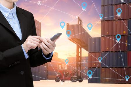 スマート ビジネスの女性は、世界中のコンテナー貨物輸送のグローバルな顧客のグローバルなビジネス接続のスマート フォンと事の技術のインター