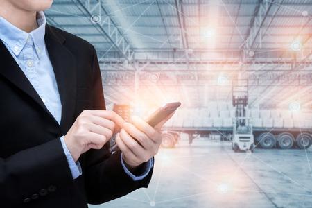 アジア ビジネスの女性は、巨大な物流配送倉庫背景と物事のインターネットのスマートな技術を使用します。フォト コンセプト、グローバル ビジ
