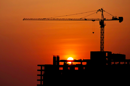 Silhouetted construction crane and building at construction site on sunset for construction industrial work concept