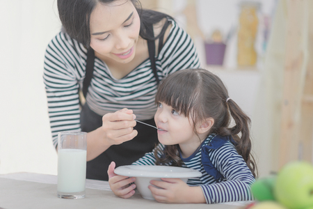 Happy family of asian mother feeding healthy breakfast to her cute daughter in the morning. Photo series of family, kids and happy people concept.