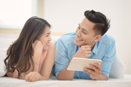 Asian couple lovers enjoy using smart tablet for shopping online together in bedroom. Couple lover happiness,family and valentine concept.