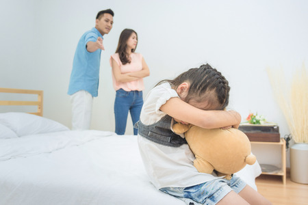 Asian little girl sadness while parent quarrelling in bedroom.Photo design for family problems and unhappy concept.