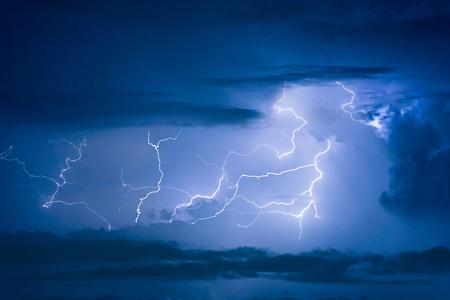 thunderhead: Thunder storm lightning strike on the dark cloudy sky background at night.