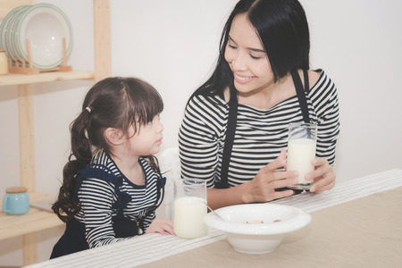 Happy family of asian mom is drinking milk with her cute daughter in the morning. Photo series of family, kids and happy people concept. Stock Photo