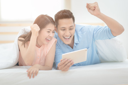 Happy Family,Asian couple lovers enjoy cheer up  and watching football sport live streaming on smart tablet.Photo series of family and happy people concept.