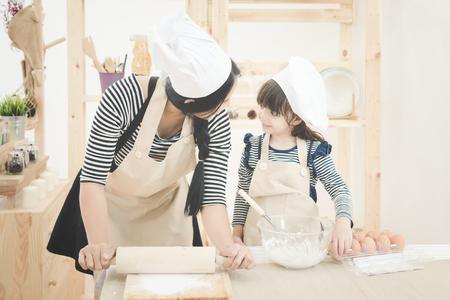 台所での幸せな家族。アジアの母と娘の生地を準備するケーキを作る。家族、子供たちと幸せな人の概念のフォト デザイン。 写真素材