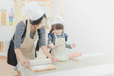 Happy family in the kitchen. Asian mother and her daughter preparing the dough to make a cake.Photo design for family, kids and happy people concept.