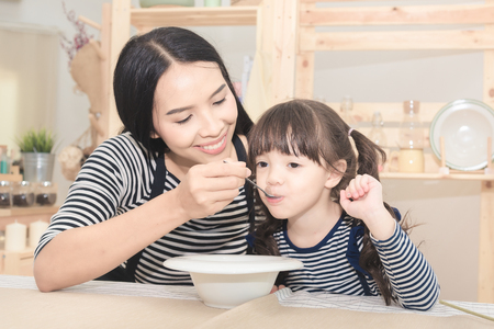 Happy family of asian mom feeding healthy breakfast to her cute daughter in the morning. Photo series of family, kids and happy people concept. Stock Photo