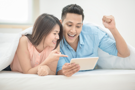 Asian couple lovers enjoy cheer up online esport on smart tablet on holiday vacation in bedroom. Stock Photo