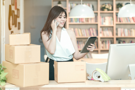 Young entrepreneur checking products stock on the smart tablet while talking to her customer at home office.Conceptual for small businesses starting own company and online marketing.