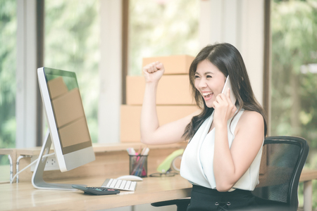 Young entrepreneur happy and celebration for achievement success mission while talking to her marketing team at home office.Conceptual for small businesses starting own company and online marketing. Stock Photo