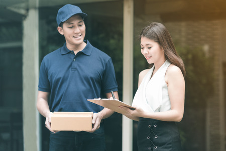 Handsome young asian delivery man smiling and holding a cardboard box while waiting beautiful young asian woman putting signature in clipboard for confirm receive.