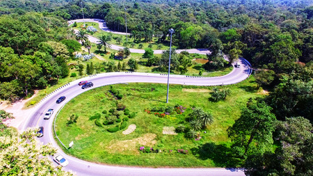 Aerial view from drone of cars are going through a curve road on the mountain with green forest. The transportation road across mountain.