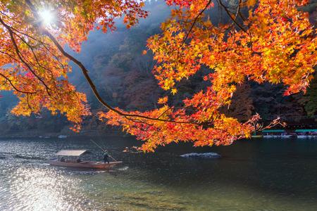 KYOTO,JAPAN-NOV26:Unidentified tourists on wooden boat enjoy autumn colors along Hozu gawa river at Arashiyama in Kyoto on November 26,2106.Arashiyama is a one of attraction landmark for tourists. Stock Photo - 96186591