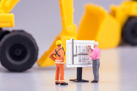 Miniature engineering people and architecture working on construction drawing. Elegant Design for industrial and construction concept. Stock Photo