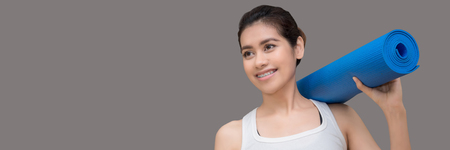 Young asian woman holding her yoga mat and charming smile while go to practice yoga exercise at the yoga sport gym.Photo design in banner cover size with copy space for add text. Stock Photo
